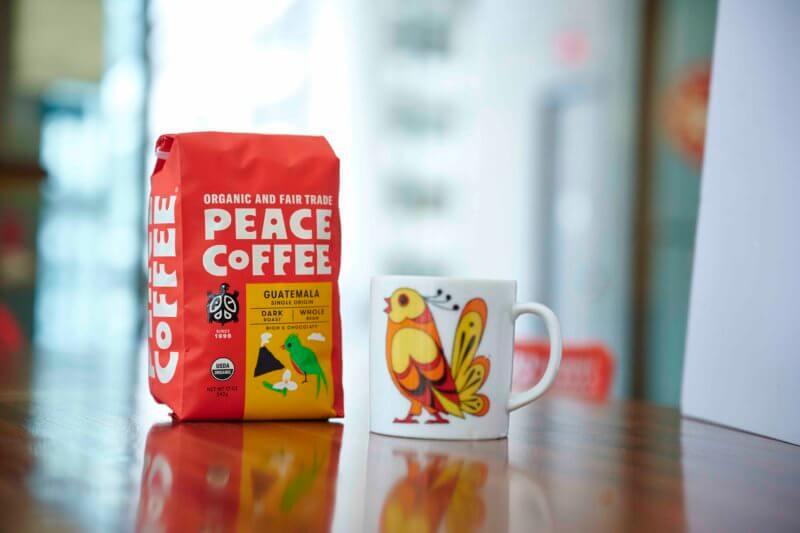bag of dark roast organic coffee with a fun mug